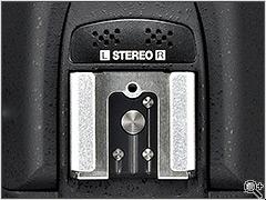 Два небольших набора отверстий перед разъемом фотовспышки скрывают стерео микрофон .Разъем для вспышки может быть использован для добавления различных аксессуаров, включая вспышку (что очевидно) и новый WR-1 беспроводной приемопередатчик.